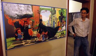 """A Pakistani man looks at a poster of the animated """"Burka Avenger"""" series on display at an office in Islamabad on Wednesday, July 24, 2014. (AP Photo/Anjum Naveed)"""