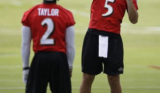 Baltimore Ravens quarterback Joe Flacco (5) throws a pass as backup quarterback Tyrod Taylor watches during an NFL football training camp practice at the team's practice facility in Owings Mills, Md., Thursday, July 25, 2013. (AP Photo/Patrick Semansky)