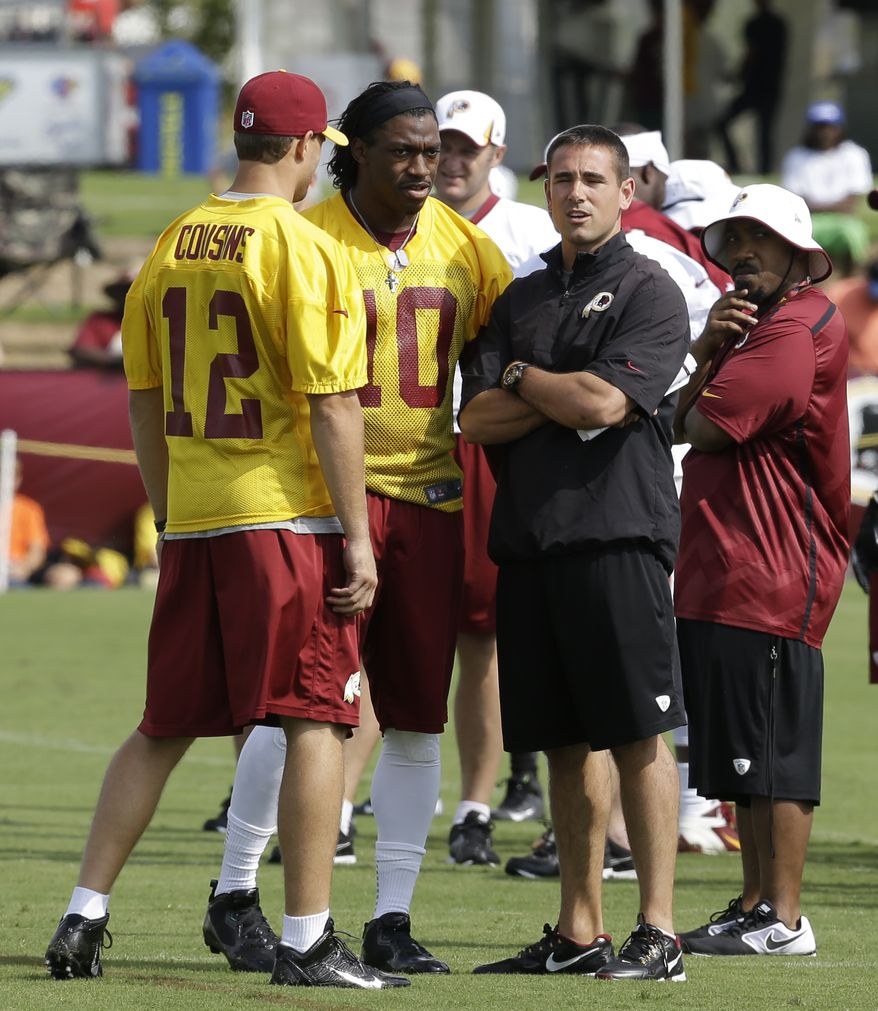 Washington Redskins quarterback coach Matt LaFleur, right, talks with quarterbacks Robert Griffin III, center, and Kirk Cousins (12) on the field as they begin their training camp at the NFL football teams new practice facility in Richmond, Va. Thursday, July 25, 2013. (AP Photo/Steve Helber)