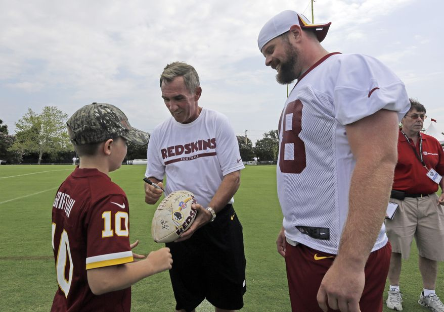 Washington Redskins head coach Mike Shanahan, center, signs an autograph for a fan as Kory Lichtensteiger, right, looks on during NFL football training camp at the team's new practice facility in Richmond, Va. Thursday, July 25, 2013. (AP Photo/Steve Helber)