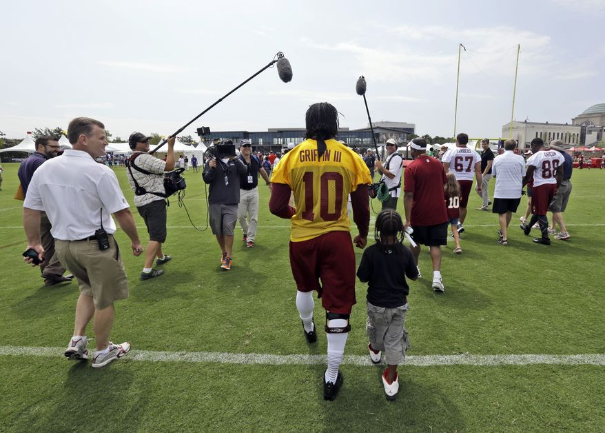 Washington Redskins quarterback Robert Griffin III walks off the field with fan Michael Dabney, 7, of Richmond, Va., during NFL football training camp at the team's new practice facility in Richmond, Va. Thursday, July 25, 2013. (AP Photo/Steve Helber)