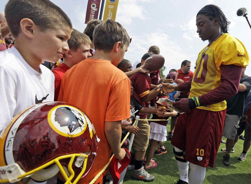 Washington Redskins quarterback Robert Griffin III signs autographs for fans during NFL football training camp at the team's new practice facility in Richmond, Va. Thursday, July 25, 2013. (AP Photo/Steve Helber)