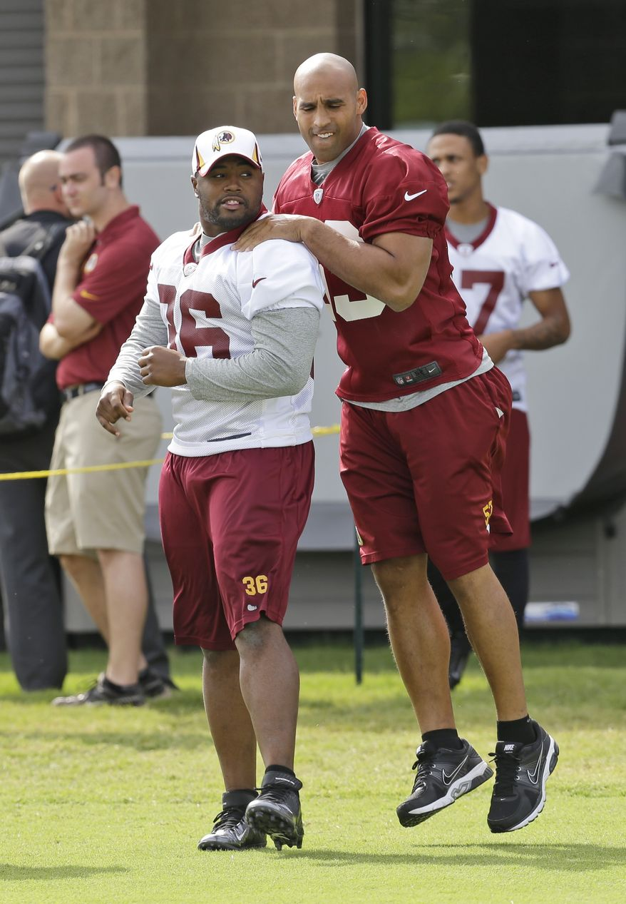 Washington Redskins Washington Redskins cornerback Josh Wilson (26) and linebacker Bryan Kehl. right, walk on the field as they begin their training camp at the NFL football teams new practice facility in Richmond, Va. Thursday, July 25, 2013. (AP Photo/Steve Helber)
