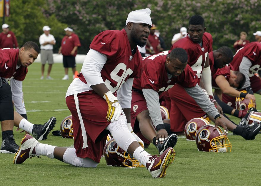Washington Redskins outside linebacker Brian Orakpo (98) stretches as the team begins their training camp at the NFL football team's new practice facility in Richmond, Va., Thursday, July 25, 2013. (AP Photo/Steve Helber)