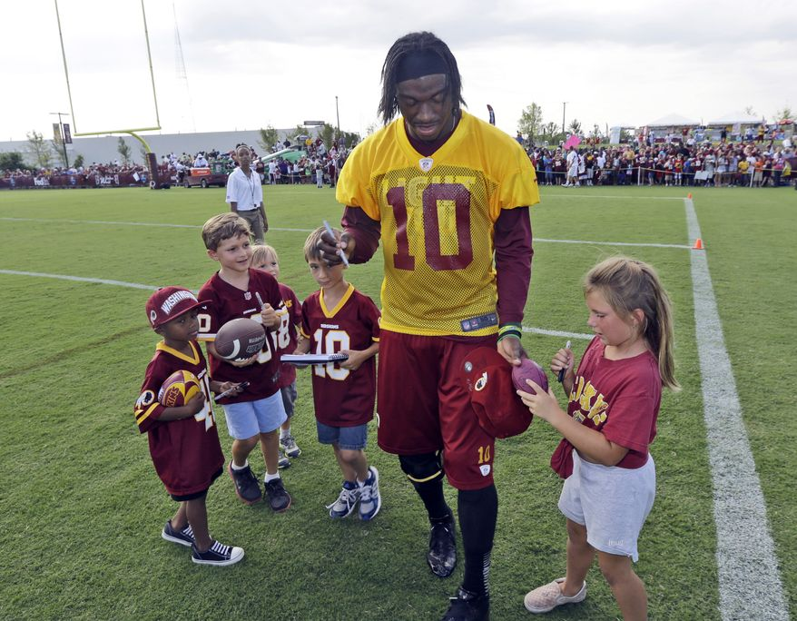 Washington Redskins quarterback Robert Griffin III signs autographs for young fans after practice at NFL football training camp in Richmond, Va., Thursday, July 25, 2013. (AP Photo/Steve Helber)