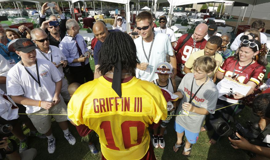 Washington Redskins quarterback Robert Griffin III signs autographs for fans after practice at NFL football training camp in Richmond, Va., Thursday, July 25, 2013. (AP Photo/Steve Helber)