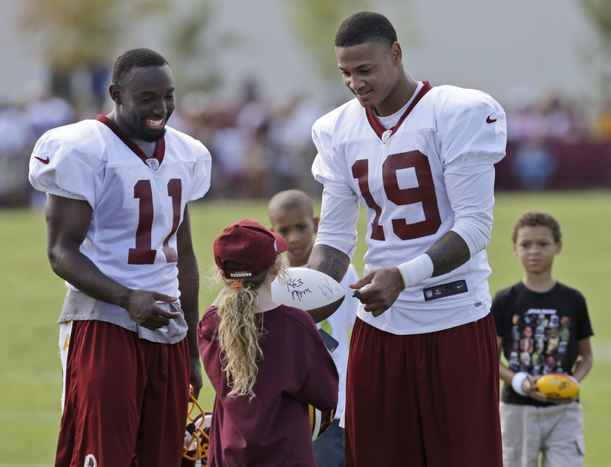 Washington Redskins wide receiver Aldrick Robinson (11) and Dezmon Briscoe (19) sign autographs for kids after practice at their first training camp at the new NFL teams practice facility in Richmond, Va. Thursday, July 25, 2013. (AP Photo/Steve Helber)