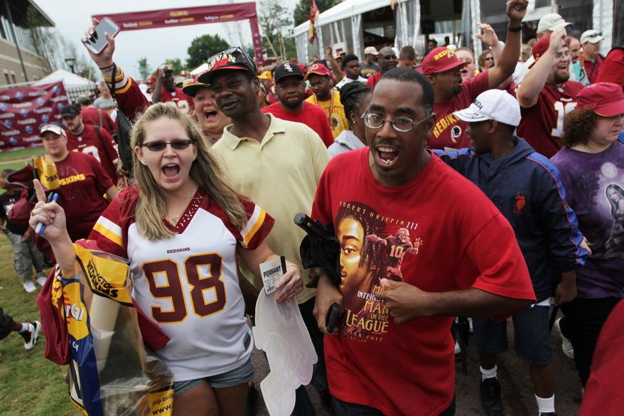 Fans run to get prime spots to watch the Washington Redskins open their NFL football training camp in Richmond, Va., Thursday, July 25, 2013. (AP Photo/The Virginian-Pilot, Steve Early)