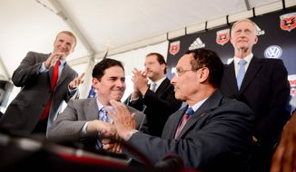 Washington, D.C., Mayor Vincent Gray, right, and D.C. United Managing Partner Jason Levien, center left, sign a deal to build a 20,000-seat soccer stadium for D.C. United in Southwest Washington just blocks from Nationals Ballpark, Washington, D.C., Thursday, July 25, 2013. (Andrew Harnik/The Washington Times)