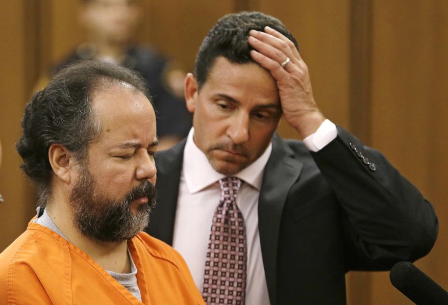 ** FILE ** Ariel Castro, left, stands before a judge with defense attorney Craig Weintraub during Castro's arraignment on an expanded 977-count indictment Wednesday, July 17, 2013, in Cleveland. Castro is charged with kidnapping and raping three women over a decade in his Cleveland home. Castro pleaded not guilty to 512 counts of kidnapping and 446 counts of rape. (AP Photo/Tony Dejak)