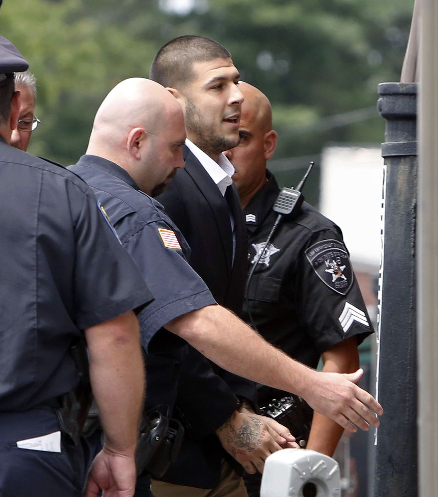 Former New England Patriots NFL football tight end Aaron Hernandez is led into Attleboro District Court, on Wednesday, July 24, 2013, in Attleboro, Mass. Hernandez has pleaded not guilty to murder in the death of Odin Lloyd. A judge rescheduled the probable cause hearing for Aug. 22, after considering defense objections to a delay. (AP Photo/Bizuayehu Tesfaye)