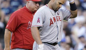 **FILE** Los Angeles Angels manager Mike Scioscia, left, walks with Albert Pujols back to the dugout after Pujols argued his called third strike in the first inning of a baseball game against the Seattle Mariners Saturday, July 13, 2013, in Seattle. (AP Photo/Elaine Thompson)