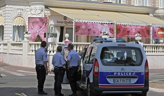 Police stand outside the Carlton Intercontinental Hotel on Sunday, July 28, 2013, in Cannes, France, the scene of the daylight robbery of a staggering $53 million worth of jewels and diamonds in one of Europe's biggest jewelry heists recent years, police said. The French Riviera hotel was hosting a temporary jewelry exhibit over the summer from the prestigious Leviev diamond house, which is owned by Israeli billionaire Lev Leviev. (AP Photo/Lionel Cironneau)