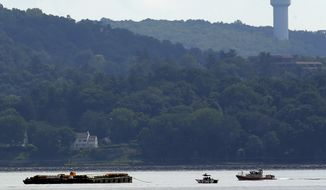 Rescue workers on boats search near a construction barge (left) on the Hudson River in Piermont, N.Y., on Saturday, July 27, 2013, south of the Tappan Zee Bridge after two people fell into the water during a boat crash. A woman's body was recovered, and authorities still are searching for a man, who is presumed dead. (AP Photo/Julio Cortez)