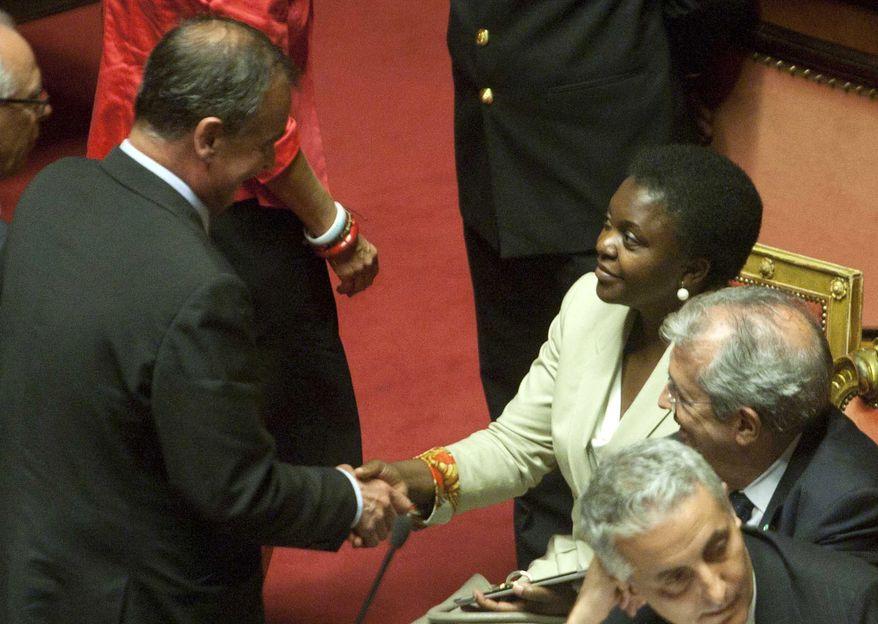 Italian Integration Minister Cecile Kyenge (top right) shakes hands with Senate Vice President Roberto Calderoli (left) inside the Senate in Rome on Tuesday, July 16, 2013. (AP Photo/Mauro Scrobogna, Lapresse)