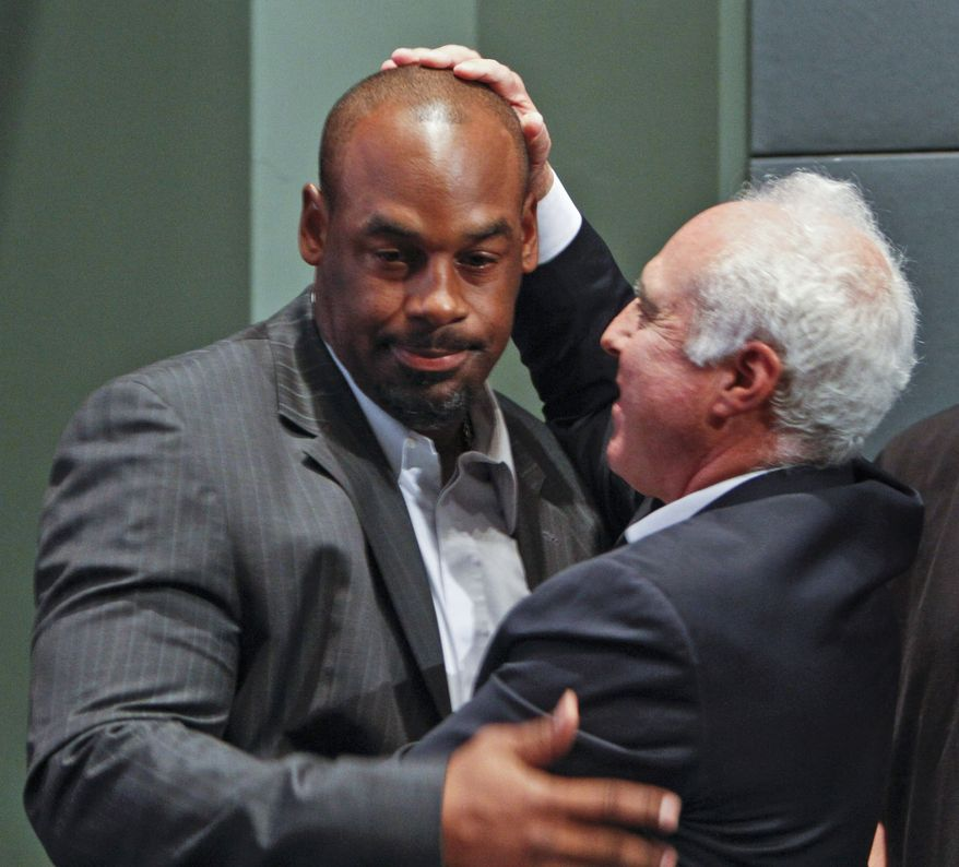 Six-time Pro Bowl quarterback Donovan McNabb, left, and Philadelphia Eagles owner Jeffrey Lurie embrace before a news conference in Philadelphia, on Monday July 29, 2013, announcing that McNabb will officially retire a member of the Eagles. McNabb played 11 of his 13 seasons with the Eagles, leading them to eight playoff appearances, five NFC East titles, five conference championship games and one Super Bowl loss. (AP Photo/ Joseph Kaczmarek)