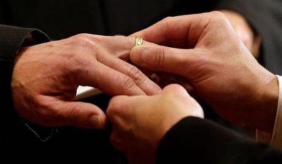 ** FILE ** Thomas Rabe (right) places a wedding ring on Robert Coffman's finger during a marriage ceremony at City Hall in Baltimore on Tuesday, Jan. 1, 2013. (AP Photo/Patrick Semansky)