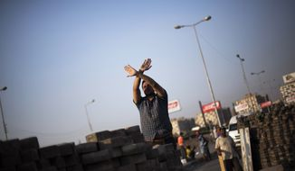 A supporter of Egypt's ousted President Mohammed Morsi stands behind a makeshift barricade in Nasr City, where protesters have installed a camp and hold daily rallies, in Cairo on Monday, July 29, 2013. Europe's top diplomat urged Egypt's government to reach out to the Muslim Brotherhood as she worked Monday to mediate an end to the country's increasingly bloody crisis, while the mainly Islamist protesters calling for the return of ousted leader Mohammed Morsi massed for more protests. (Associated Press)