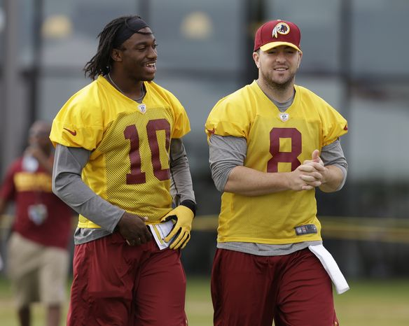 Washington Redskins quarterbacks Robert Griffin III (10) and Rex Grossman (8) walk to the field during the NFL football teams training camp in Richmond, Va. Monday, July 29, 2013. (AP Photo/Steve Helber)