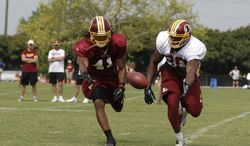 Washington Redskins tight end Emmanuel Ogbuehi, right, and strong safety Phillip Thomas, reach for a pass during the NFL football teams training camp in Richmond, Va. Saturday, July 27, 2013. (AP Photo/Steve Helber)
