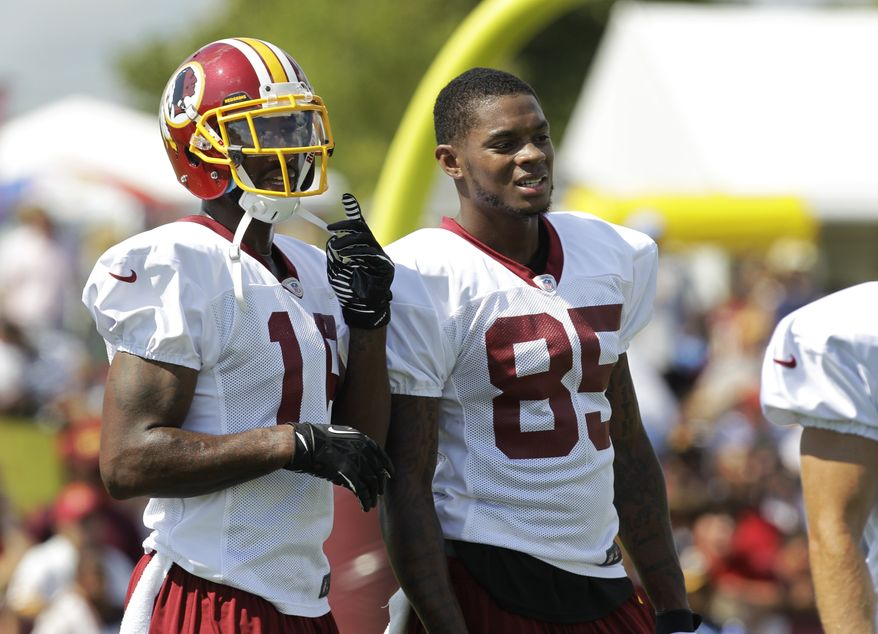 Washington Redskins wide receiver Josh Morgan, left, and Leonard Hankerson (85) watch practice during the second day of the NFL football teams training camp in Richmond, Va. Friday, July 26, 2013. (AP Photo/Steve Helber)