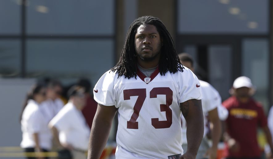 Washington Redskins guard Adam Gettis (73) walks to the field during the second day of the NFL football teams training camp in Richmond, Va. Friday, July 26, 2013. (AP Photo/Steve Helber)