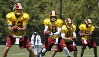 Washington Redskins quarterbacks Kirk Cousins (12), Robert Griffin III (10), Rex Grossman (8), and Pat White (5) participate in a drill during the afternoon practice at the NFL football team's training camp in Richmond, Va., Monday, July 29, 2013. (AP Photo/Steve Helber)