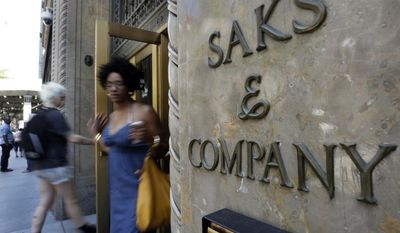 Shoppers use a Fifth Avenue entrance to Saks in New York on Monday, July 29, 2013. Saks Inc. agreed to be acquired by Hudson's Bay Co., the Canadian parent of upscale retailer Lord & Taylor, for about $2.4 billion in a deal that will bring luxury to more North American locales. (AP Photo/Richard Drew)