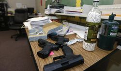 **FILE** Practice air-powered handguns sit on a teacher's desk in a classroom at Clarksville High School in Clarksville, Ark., on July 11, 2013. Twenty Clarksville School District staff members are training during the summer to be armed security guards on campus. (Associated Press)