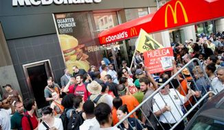 Demonstrators in support of fast food workers protest outside a McDonald's as they demand higher wages and the right to form a union without retaliation Monday, July 29, 2013, in New York's Union Square. Activists say hundreds of workers have walked off their jobs. They are demanding a minimum wage increase and calling for better benefits. (AP Photo/John Minchillo)