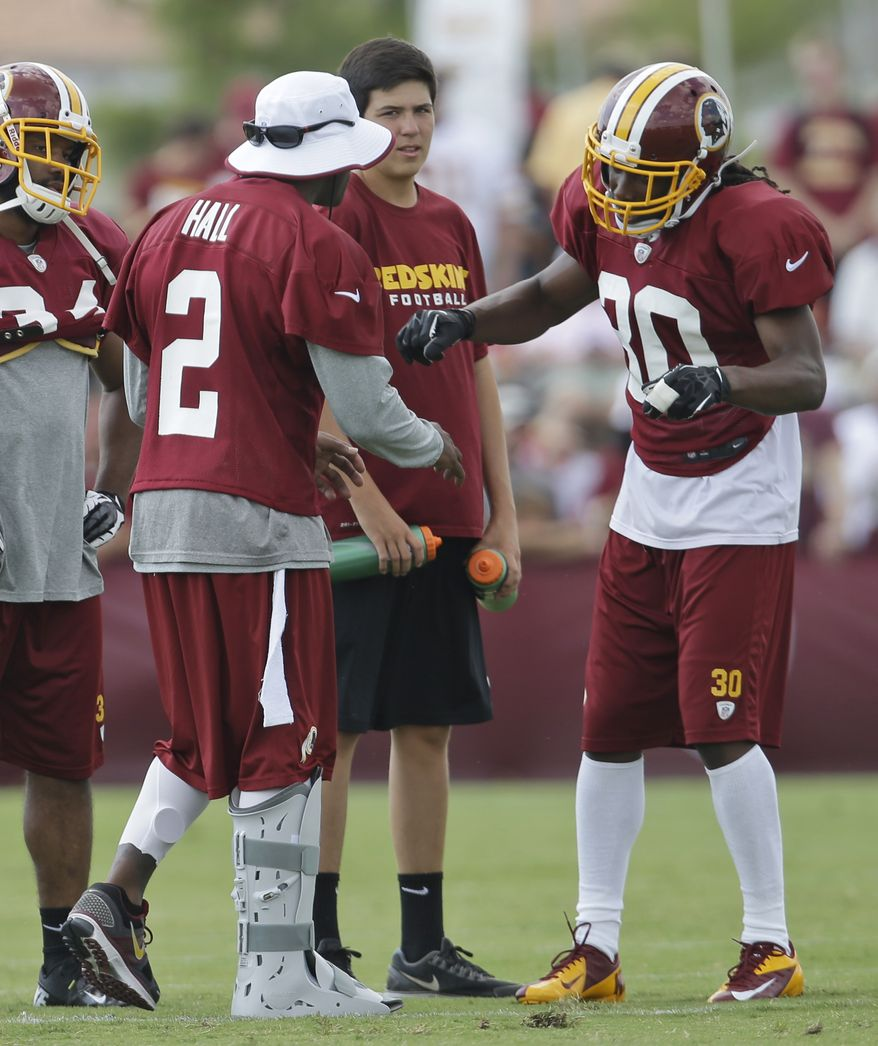 Washington Redskins cornerback DeAngelo Hall (2), wearing a boot on his injured foot, talks with cornerback E.J. Biggers (30) during afternoon practice at the NFL football team's training camp in Richmond, Va., Tuesday, July 30, 2013. (AP Photo/Steve Helber)
