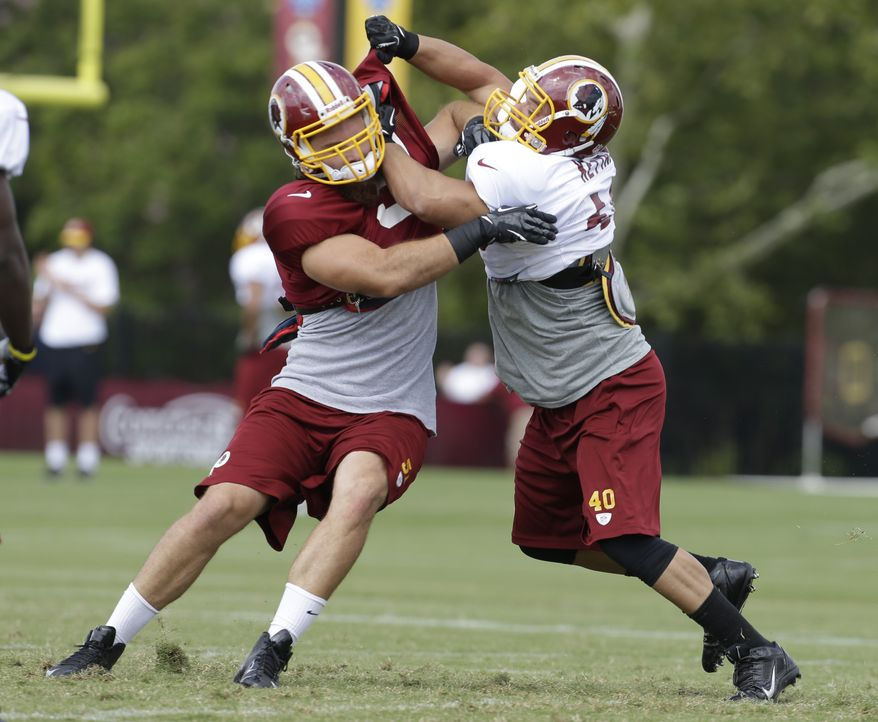 Washington Redskins linebacker Ricky Elmore, left, tries to get by fullback Eric Kettani, right, during afternoon practice at NFL football training camp in Richmond, Va., Tuesday, July 30, 2013. (AP Photo/Steve Helber)