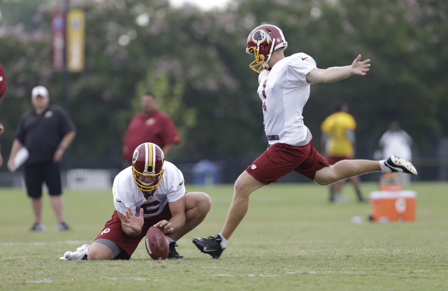 Washington Redskins kicker John Potter (1) practices field goals as Sav Rocca, left, holds during the morning practice at the NFL football teams training camp in Richmond, Va. Wednesday, July 31, 2013. (AP Photo/Steve Helber)