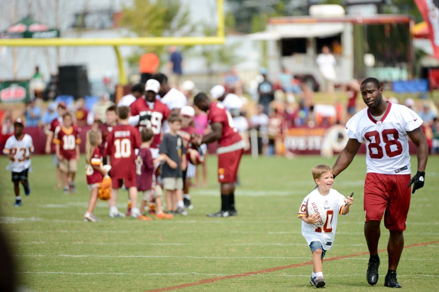 Washington Redskins wide receiver Pierre Garcon (88) spends time with children signing autographs after morning walkthroughs at the Bon Secours Washington Redskins Training Center, Richmond, Va., Tuesday, July 30, 2013. (Andrew Harnik/The Washington Times)