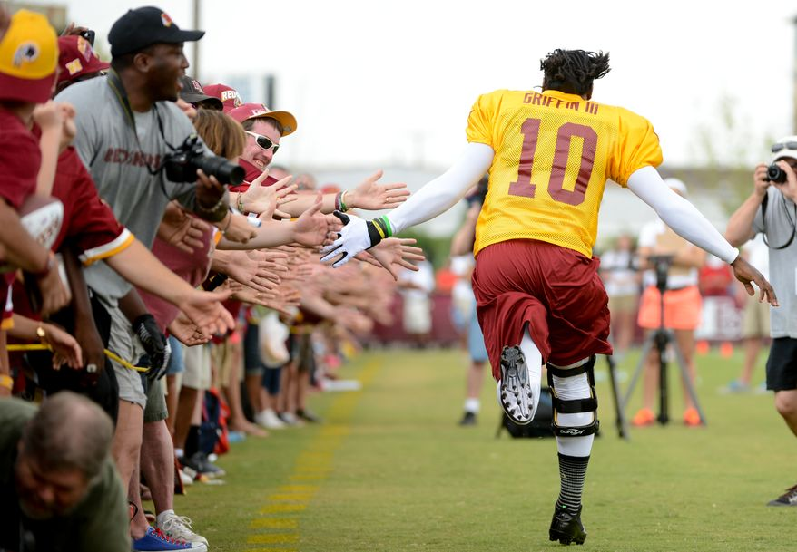 Washington Redskins quarterback Robert Griffin III (10) gets high fives from fans as he runs the length of the field before afternoon practice at the Bon Secours Washington Redskins Training Center, Richmond, Va., Tuesday, July 30, 2013. (Andrew Harnik/The Washington Times)
