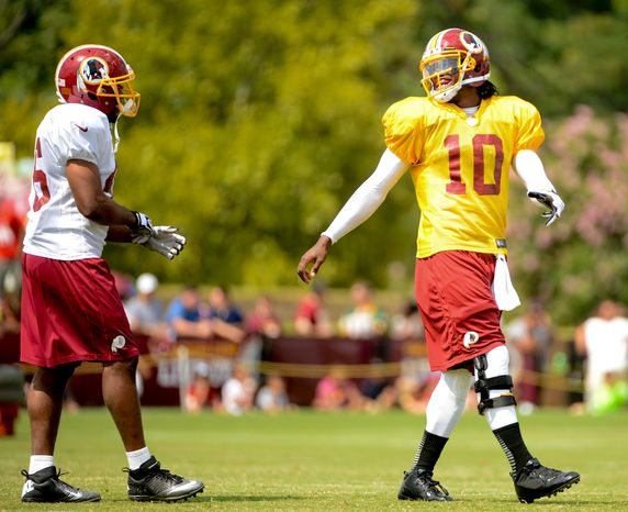 Washington Redskins quarterback Robert Griffin III (10) shares a laugh with Washington Redskins running back Alfred Morris (46), left, during afternoon practice at the Bon Secours Wash
