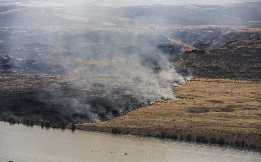 This Monday, July 29, 2013, photo shows the Colockum Pass fire burning in the mountains and which has also burned its way down to the banks of the Columbia River. The Colockum Pass fire has grown to more than 10 square miles burning 5 five homes in addition to other structures 20 miles south of Wenatchee. (AP Photo/The Seattle Times, Steve Ringman)