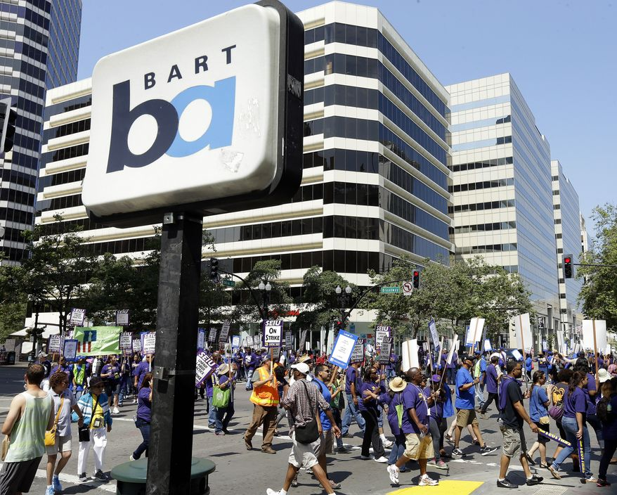 ** FILE ** In this file photo from Monday, July 1, 2013, striking Bay Area Rapid Transit workers picket as they close the intersection of 14th & Broadway in downtown Oakland, Calif. The two sides were set to resume negotiations at noon on Thursday, Aug. 1, but did not appear close to an agreement. (AP Photo/Ben Margot)