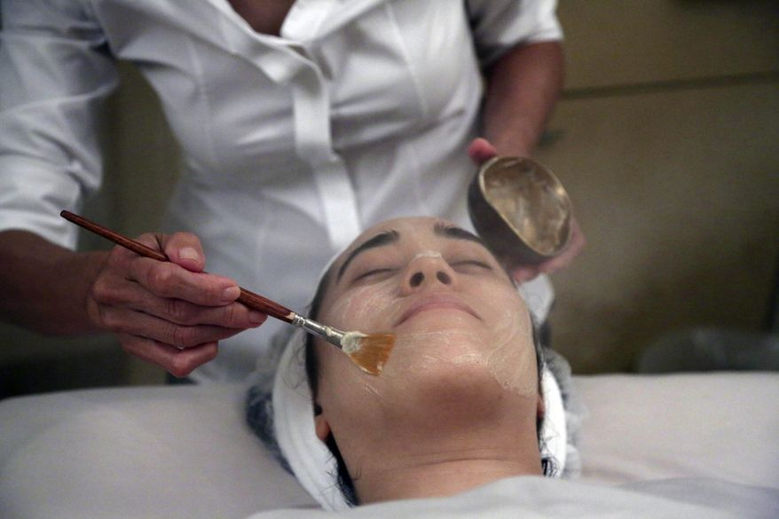 Salon owner Shizuka Bernstein gives what she calls a Geisha Facial to Mari Miyoshi at Shizuka New York skin care in New York. The facial, which Bernstein has been offering for five years, is a traditional Japanese treatment using imported Asian nightingale excrement mixed with rice bran. (AP Photo/Mary Altaffer)