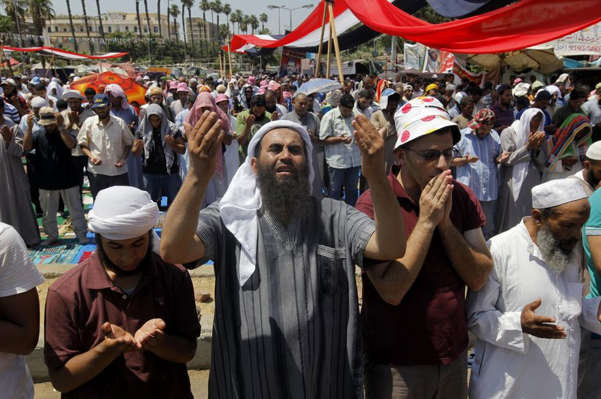 """Supporters of Egypt's ousted President Mohammed Morsi attend Friday prayers at a camp near Cairo University in Giza, southwest of Cairo, Egypt, Friday, Aug. 2, 2013. An international human rights group has warned of a """"bloodbath"""" if Egypt's new leadership uses force to end sit-ins by loyalists of the country's ousted president. (AP Photo/Amr Nabil)"""