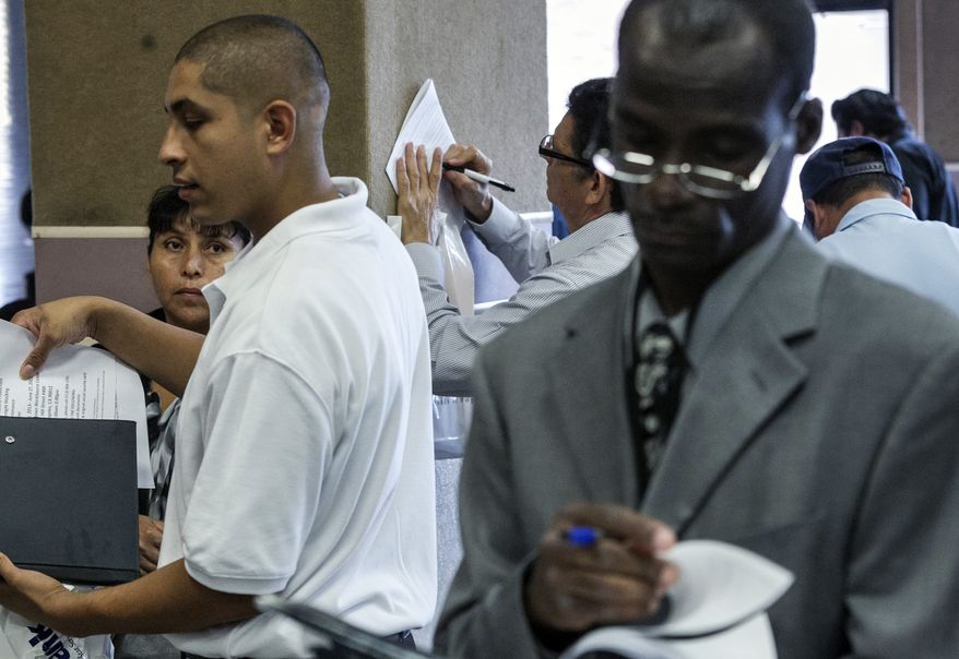 ** FILE ** In this Thursday, June 6, 2013, photo, job seekers apply for prospect employment positions at the 12th annual Mission career fair in the Skid Row area of Los Angeles. (AP Photo/Damian Dovarganes)