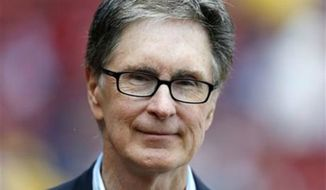 ** FILE ** Boston Red Sox owner John Henry stands on the field before a baseball game in Boston, May 11, 2013. The principal owner of the Boston Red Sox has entered into an agreement to buy The Boston Globe.  (Associated Press)