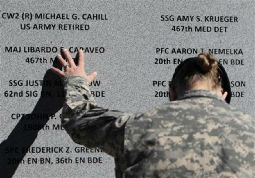Staff Sgt. Joy Clark of the 467th Combat Stress Control Detachment takes a moment to run her fingers over the engravings of the names of her fellow soldiers at a ceremony commemorating the one-year anniversary of the worst mass shooting on a U.S. military base, in Fort Hood, Texas, on Nov. 5, 2010. Maj. Nidal Hasan is charged in the 2009 shooting rampage at Fort Hood that left 13 dead and more than 30 others wounded. (Associated Press) **FILE**