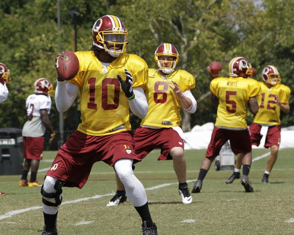 Washington Redskins quarterback Robert Griffin III (10) Rex Grossman (8), Pat White (5) and Kirk Cousins (12) look for receivers during the afternoon practice at the NFL football team's training camp in Richmond,Va. Friday, Aug. 2, 2013. (AP Photo/Steve Helber)