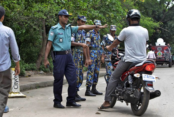 Bangladeshi police stop a motorist for checking in front of the U.S. Embassy building that remained closed due to security threat in Dhaka, Bangladesh, Sunday, Aug. 4, 2013. (AP Photo/A.M. Ahad)