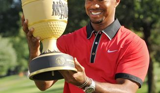 Tiger Woods holds the trophy after winning the Bridgestone Invitational golf tournament Sunday, Aug. 4, 2013 at Firestone Country Club in Akron, Ohio. Woods' 15-under par won by seven shots. (AP Photo/Phil Long)
