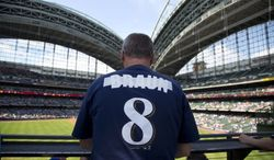 Bryan Von Declan has the name of Milwaukee Brewers suspended player Ryan Braun covered up in his shirt as he takes his seat before the baseball game between the San Diego Padres and the Brewers Thursday, July 25, 2013, in Milwaukee. (AP Photo/Jeffrey Phelps)