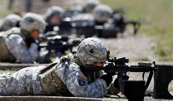 Female soldiers test body armor while training in Fort Campbell, Ky. According to a review of statements, the military may be lowering some physical standards for male and female troops on the argument that certain tasks are outdated or irrelevant. (Associated Press)