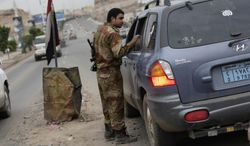 """A Yemeni soldier inspects a car at a checkpoint on a street leading to the U.S. embassy in Sanaa, Yemen, on Aug. 4, 2013. Security forces close access roads, put up extra blast walls and beef up patrols near some of the 21 U.S. diplomatic missions in the Muslim world that Washington ordered closed for the weekend over a """"significant threat'' of an al Qaeda attack. (Associated Press)"""