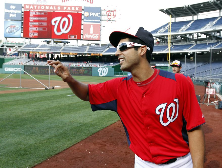 Washington Nationals starting pitcher Gio Gonzalez (47) reacts with members of the Atlanta Braves before a baseball game at Nationals Park, Monday, Aug. 5, 2013, in Washington. (AP Photo/Alex Brandon)
